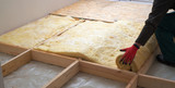 Work composed of mineral wool insulation in the floor, floor heating insulation , warm house, eco-friendly insulation, a builder at work - 190240578