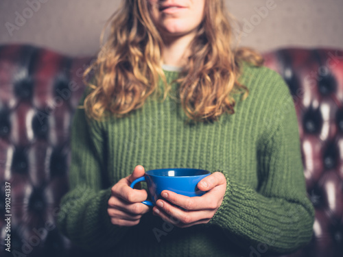 Young woman in living room with cup