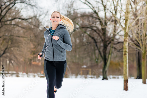 Fotobehang Hoogte schaal Woman running or jogging down a path on winter day in park