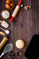 Ball of fresh raw dough near ingedients and cookware on dark wooden background top view space for text