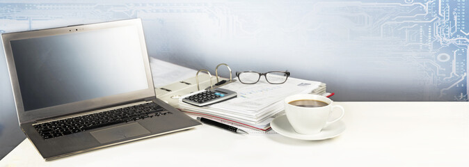 laptop computer, folder, calculator and a cup of coffee on a white office desk, digital business concept with copy space, panoramic banner format background © Maren Winter