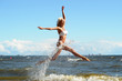 Quadro beautiful blonde in a swimsuit is jumping near the sea
