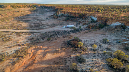 Aerial view of four wheel drive vehicle and caravan camped in the outback of Australia