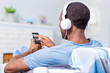 Music playlist. Pleasant nice handsome man wearing headphones and holding his smartphone while choosing the song