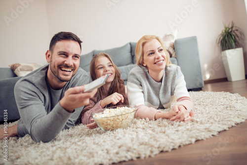 Smiling young family watching TV together.