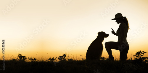 Web banner of a dog and his female trainer - silhouette image with blank, copy space