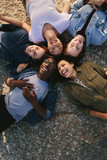 Diverse friends lying on ground in circle outdoors - 190359754