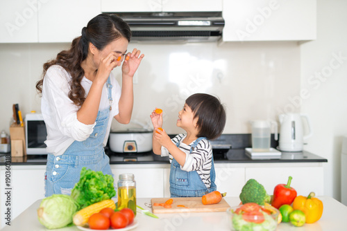 Wall mural Mother with her daughter in the kitchen cooking together
