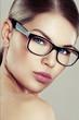 Fashion female in stylish eyeglasses over studio background. Eyesight correction concept.