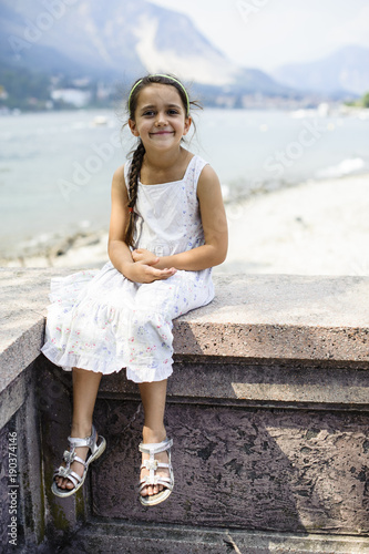 Poster portrait of a 7 year old girl sitting on a wall