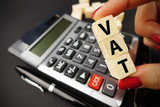 VAT text on wooden cubes above office calculator suggesting tax time or payment  - 190390749