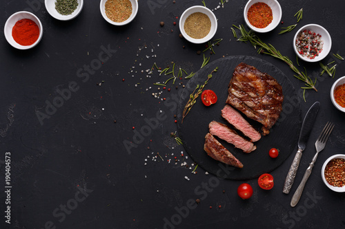 Rib eye steak and spices on black background - 190404573