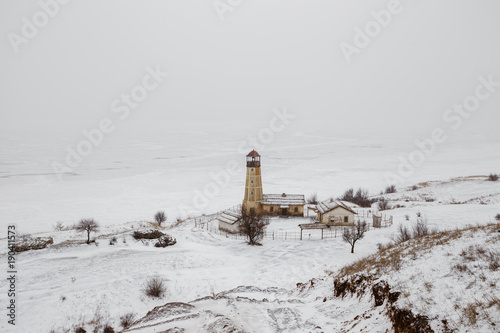 Aluminium Vuurtoren Old wooden lighthouse at edge of frozen harbor with cloudy sky