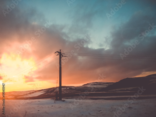 Fotobehang Betoverde Bos Magic landscape with snow, hills and an electricity pillar
