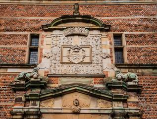Hillerod, Denmark - September, 23th, 2015. Copper lion sculptures and blazon on brick wall of Frederiksborg castle near Copenhagen.