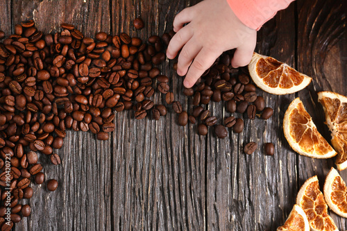 Poster Koffiebonen Coffee beans are sprinkled on a wooden table with the decor of dried oranges. Next to children's hands
