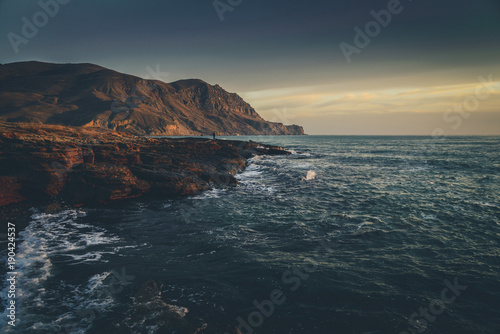 In de dag Nachtblauw Wavy sea at sunset at the rocky coastline