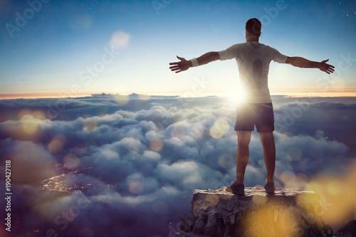 Fototapeta Mann über den Wolken breitet Arme aus
