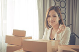 Happy Start up business woman sitting in a desk full of delivery boxes - 190429345