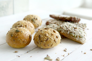Bread buns with various seeds on white wooden table. Bread roll and breadsticks with sesame, pumpkin, sunflower, flax seeds,