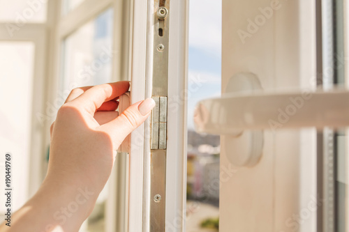 Foto Murales Woman's hand opening pvc window on the background of high-rise buildings in sunny day. Closeup shot
