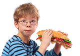 boy eating large sandwich on white background - 190455312