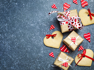 Gift box with decorative red hearts and heart shaped cookies. Festive background. Flatlay with copy space.