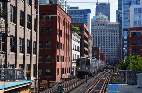 Papiers peints Chicago An elevated commuter train passes old warehouse buildings in Chicago.