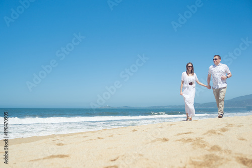 Young romantic couple walking on the beach