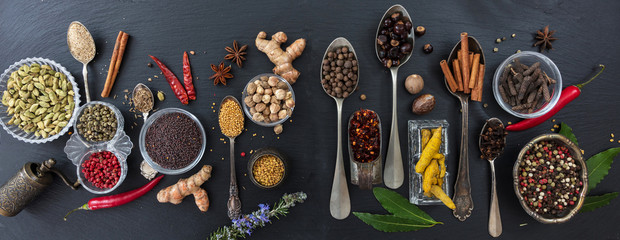 Variety of colorful spices and herbs on black stone background, top view, banner © Rawf8