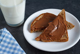 Slice of bread with chocolate cream and a glass of milk - 190496761