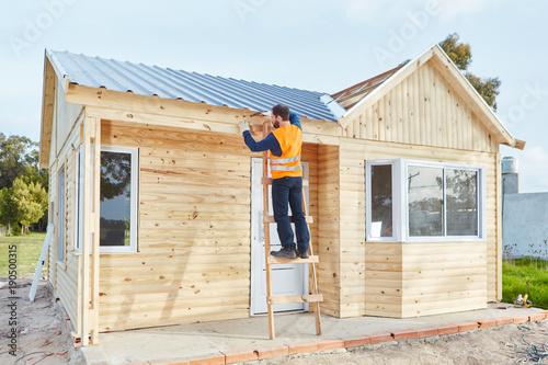 Handwerker arbeitet am Neubau von Holzhaus - 190500315