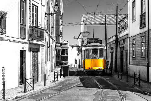 Yellow tram on old streets of Lisbon, Portugal, popular touristic attraction and destination. Black and white picture with a coloured tram. - 190504729