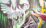 Street artist painting colorful monster graffiti on public wall - Modern art concept with urban guy performing and preparing live murales with multi color aerosol spray - Focus on hand