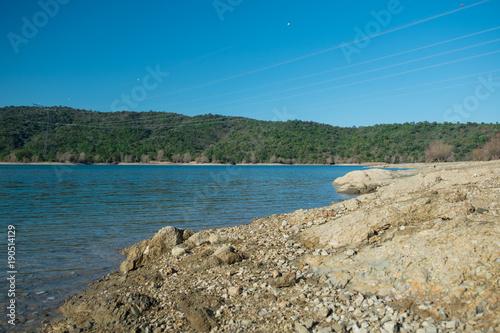 Foto op Canvas Groen blauw Steiniges Seeufer unter blauem Himmel
