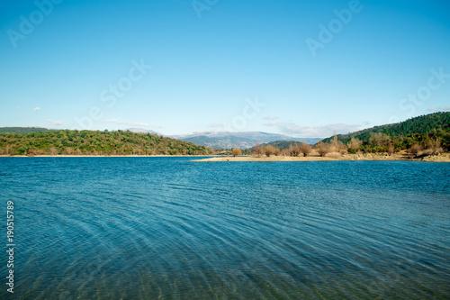 Fotobehang Blauw See mit Panoramablick auf Bergkette unter blauem Himmel