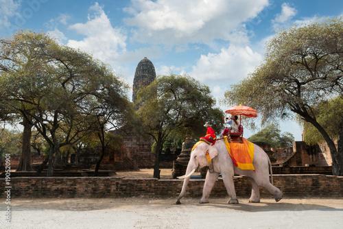 Couple tourists riding elephant ride around Ayutthaya historic site looking Wat Phra Ram temple at Ayutthaya, Thailand.
