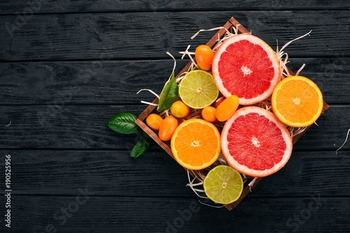 Kumquat, orange and grapefruit. Fresh Tropical Fruits. On a wooden background. Top view. Copy space.