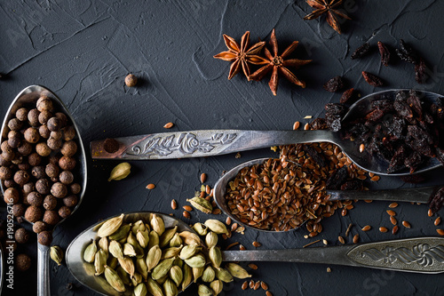 Poster Koffiebonen Various spices spoons on stone table.On dark concrete background.Herbs and spices on wooden table. Top view with space for your text