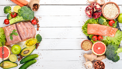 Foto Murales Healthy food background. Concept of Healthy Food, Chicken Fillet, Raw Meat, Fish, Avocado, Broccoli, Fresh Vegetables, Nuts and Fruits. On a wooden background. Top view. Copy space.