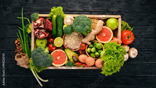 The concept of healthy food. Fresh vegetables, nuts and fruits in a wooden box. On a wooden background. Top view. Copy space. - 190526761