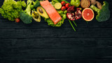 Healthy food. Fish salmon, avocado, broccoli, fresh vegetables, nuts and fruits. On a black background. Top view. Copy space. - 190526939