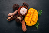 Mangosteen, mango, tamarind and rambutan. Fresh Tropical Fruits. On a wooden background. Top view. Copy space. - 190527150