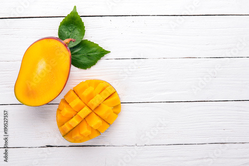 Mango. Tropical Fruits. On a wooden background. Top view. Copy space. © Yaruniv-Studio