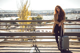 Woman standing baggage at handrail - 190529312