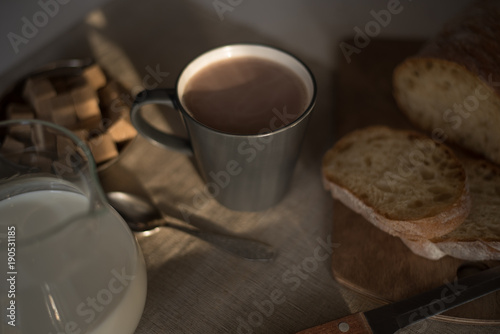Foto op Canvas Chocolade Mug of hot chocolate, milk and bread on a wooden background in the early morning
