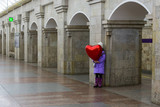 The girl with a red balloon in the shape of a heart on the subway platform. Valentine's day