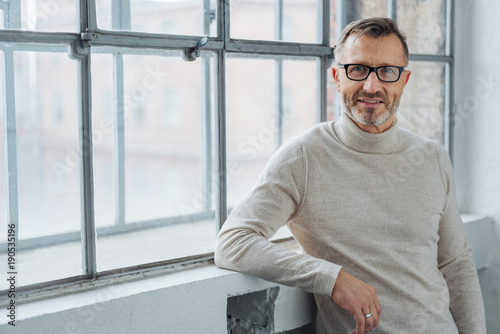 Leinwandbild Motiv Smiling attractive mature man wearing glasses
