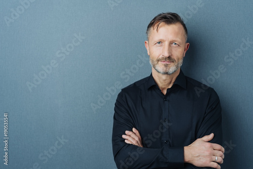 Leinwanddruck Bild Serious middle-aged man with folded arms