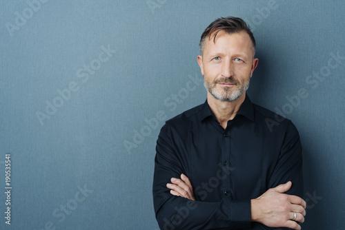 Leinwandbild Motiv Serious middle-aged man with folded arms